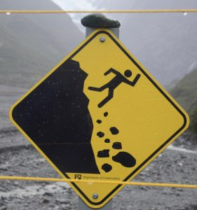 Warning sign of man chasing rocks off a cliff.