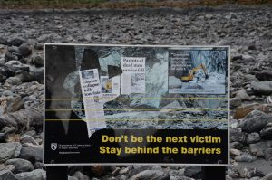 Warning sign telling people to stay behind the barriers near a glacier with threats of death if ignored.
