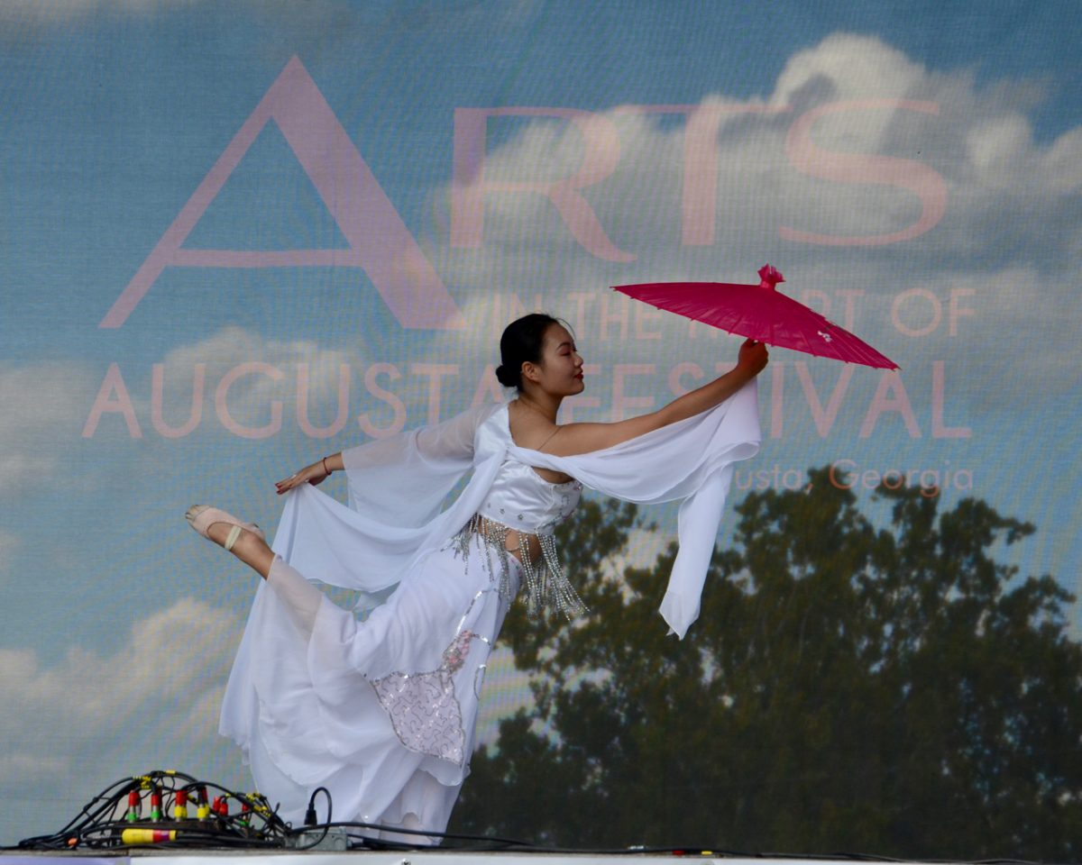 Chinese woman in white, dancing with a pink parasol.