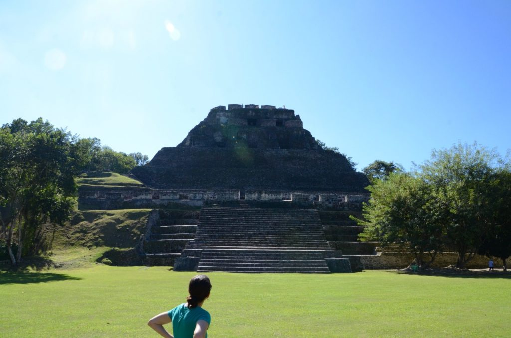 A woman looking at a large Mayan stone temple at the edge of green grass.