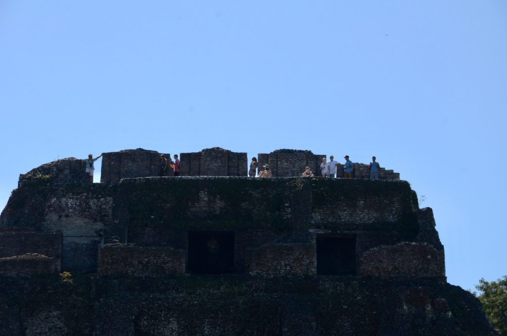 People on the top of a large stone temple.