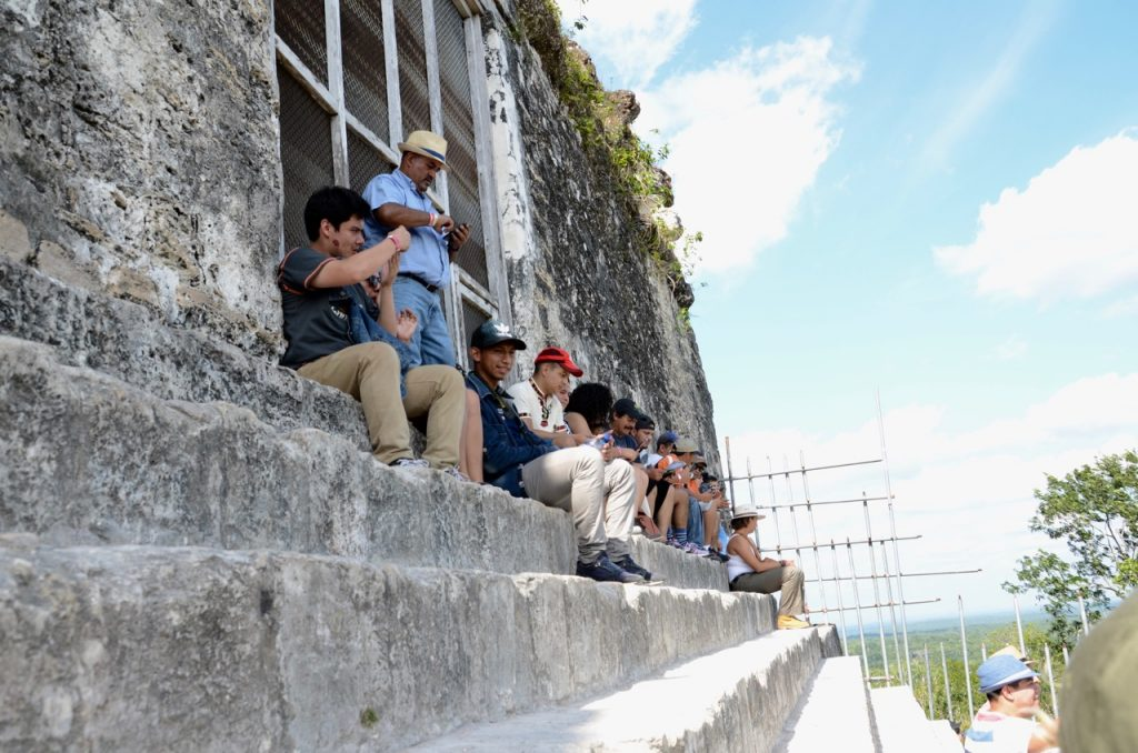 Several people sitting on stone steps with a weak fence behind them, but not in front.