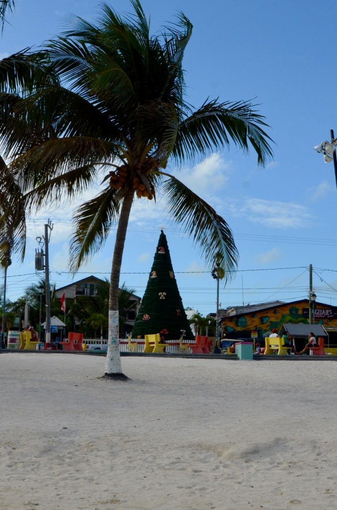 A fake christmas tree on a beach next to palm trees