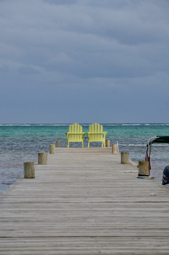 Yellow chairs at the end of a dock on the ocean.