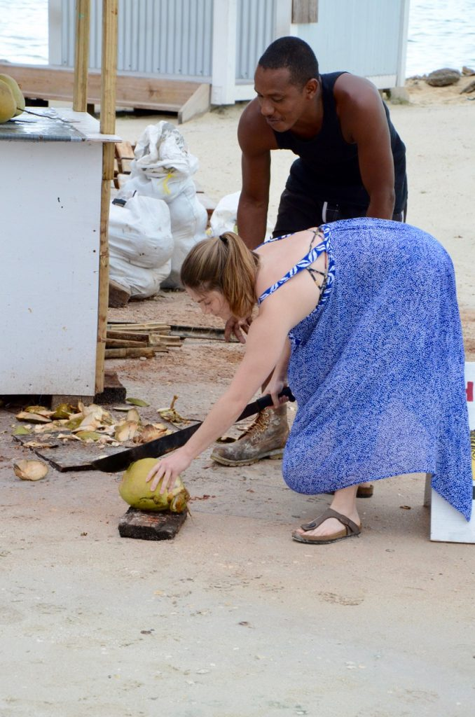 Woman cutting a coconut with a machete.