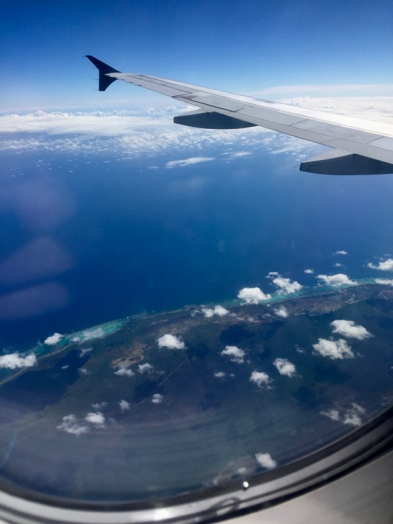 View out the window of an airplane showing the wing, ocean, and Belize coast line.