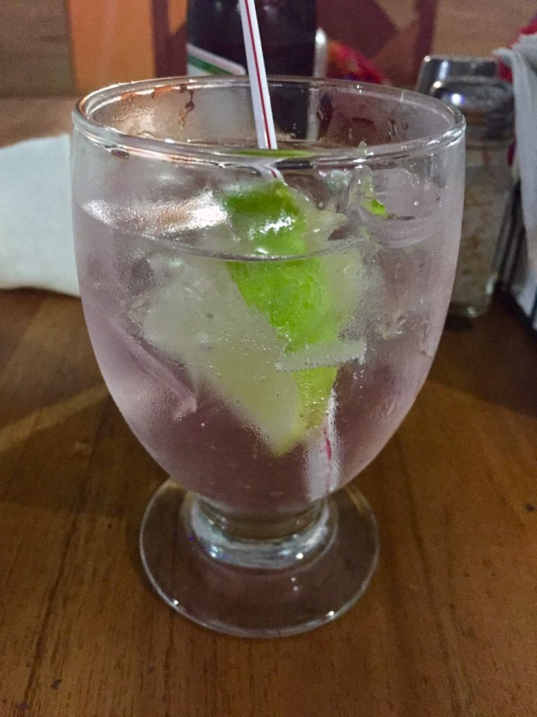 A gin and tonic with a light pink tint.