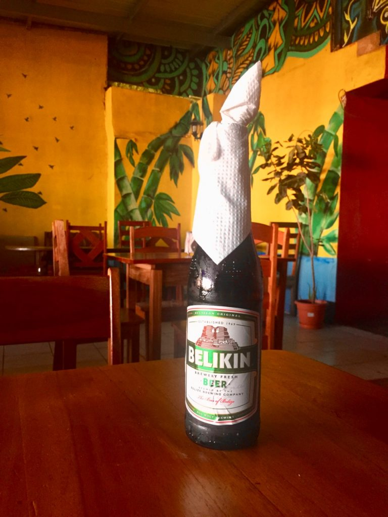 A bottle of Belikin beer with a napkin around the top.