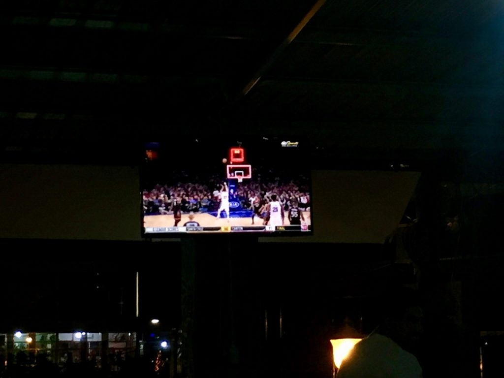 Fuzzy picture of a Sixers game on a bar TV.
