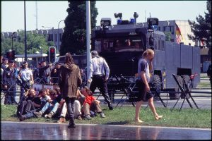 A wet older man standing in front of the water cannon truck with lots of younger people on the ground around him.