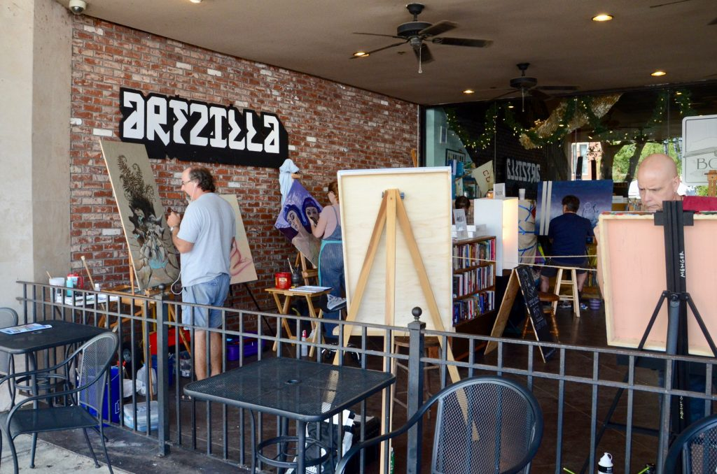 "A group of painters working in an open air space with ""artzilla"" painted on the wall behind. Several partial paintings can be seen as the artists work."