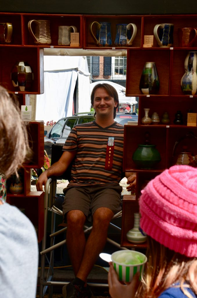 A smiling male potter of European decent, wearing an badge marking him as the artist, sits in his booth framed by pieces he is selling as festival goers review his wears.