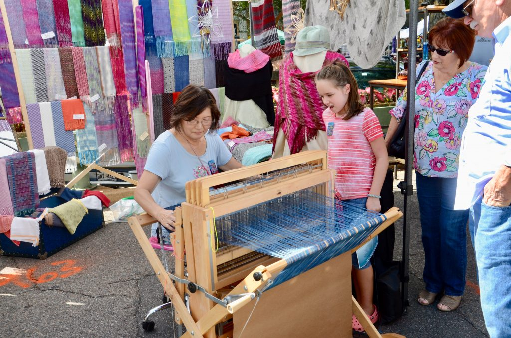 A woman of Asian decent is weaving on a moderate sized loom while a little girl of European decent watches excitedly.  Several scarves and table runners are mounted in the background for display and sale.