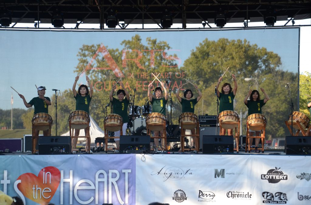 Image shows a collection of women of Chinese decent with green t-shirts with drum sticks raised as they perform on a large outdoor stage.