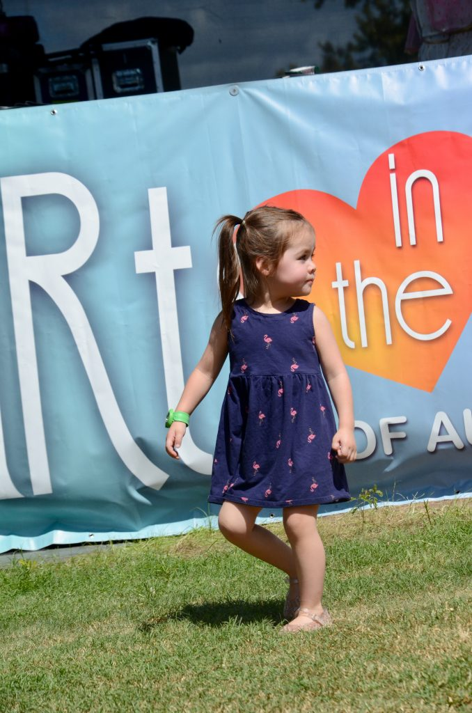 A little girl playing on the green in front of the banner reading Arts in the Heart, looking over her shoulder to check that she knows where her family is.