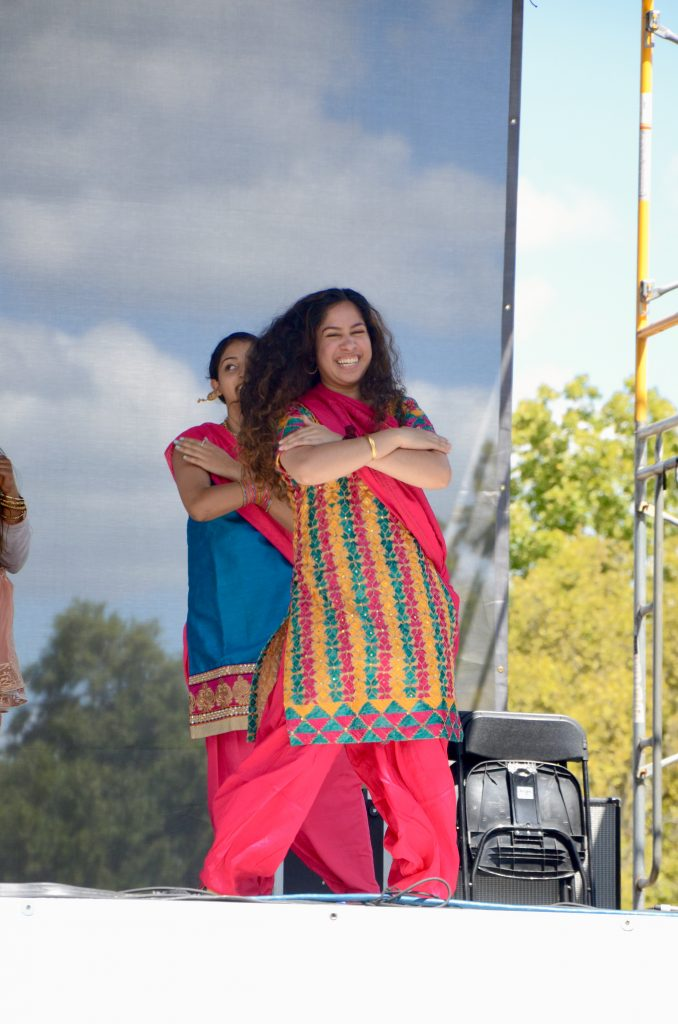 A young woman of Indian decent wearing a bright Shalwar kameez smiles as she dances.