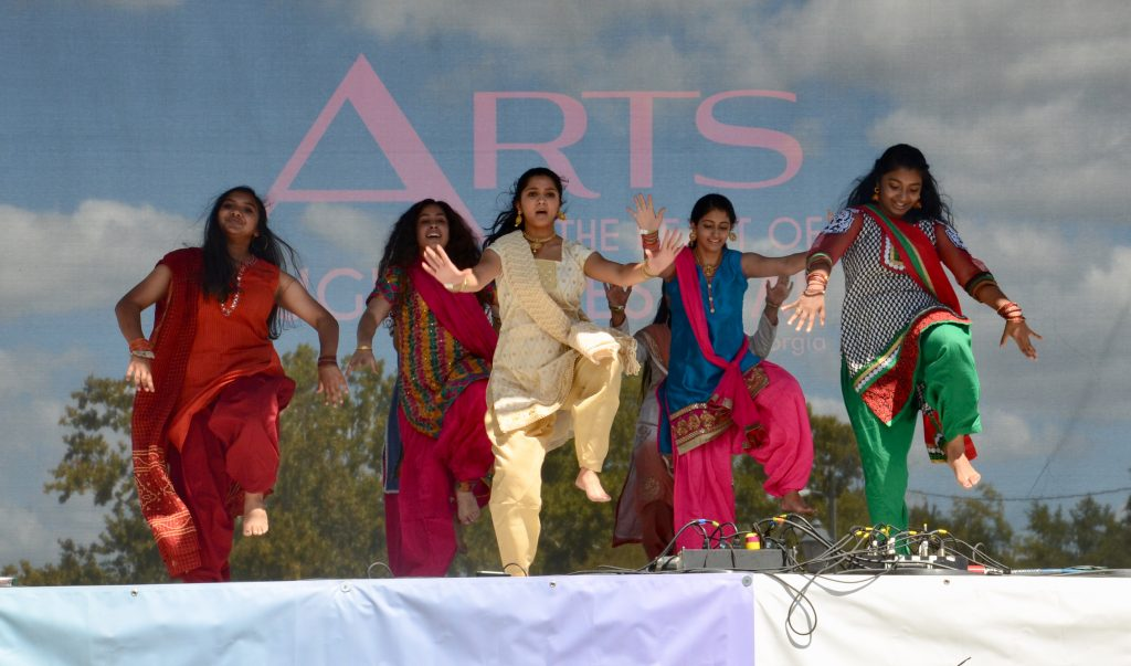 A group of teenagers from the Hindu temple society dance in their traditionally bright costumes on the main stage.