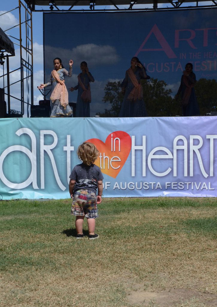 A little boy standing on the main green in front of the Arts in the heart banner watching some girls from the Hindu temple society dance.