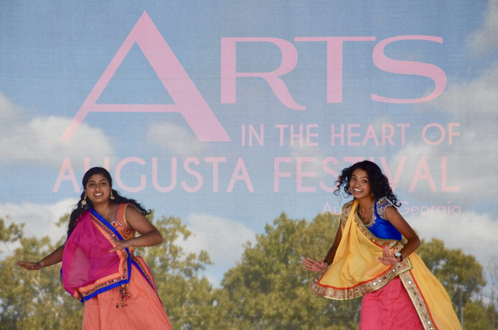 A pair of college women from the Hindu temple society in brightly colored costumes dance in front of the backdrop labeled for the festival.