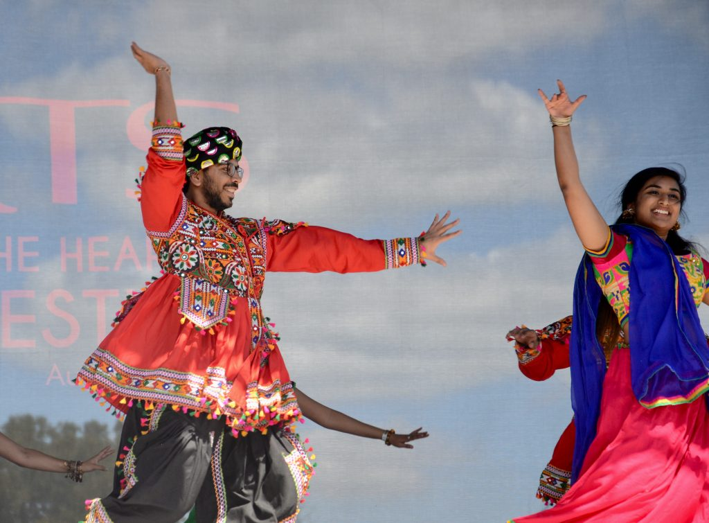 A college aged man from the Hindu temple society in a bright red costume dances next to some young women of the group. Everyone smiling and enjoying themselves.
