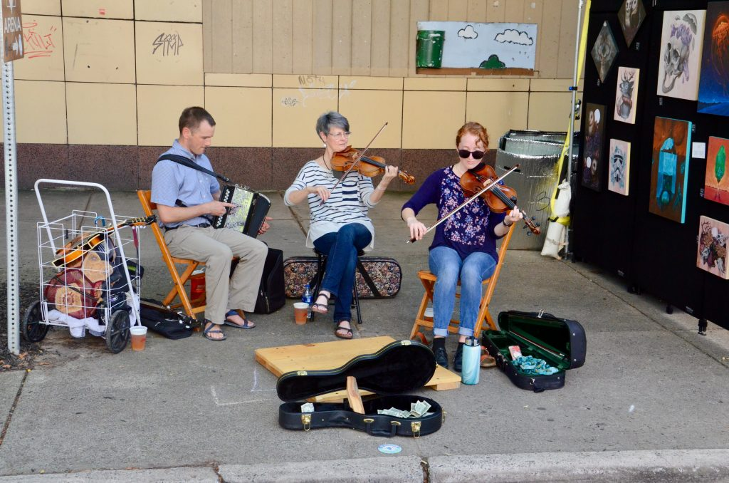 A group of adults are performing on the street. Two women on violins, and a man on the accordion. Cases are open to accept tips, and they seem to be doing well.