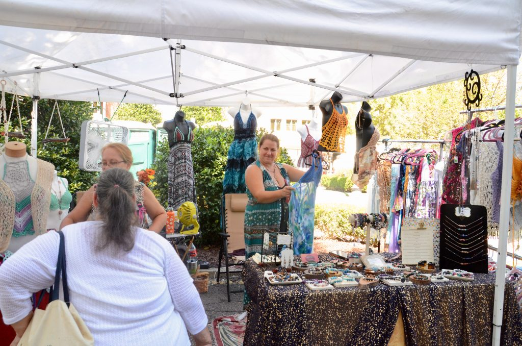 A woman selling crocheted dresses and women's tops stands at her table showing her wears to festival goers.
