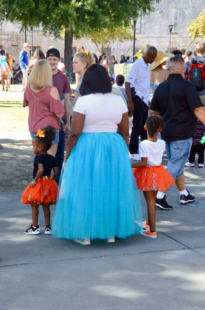 A large African American woman, with two little girls standing at the edge of a crowd facing away. Each dressed in a t-shirt and tool skirt. The mother's is long and blue, the little girls' are short and red. They are clearly either just finished a performance or are about to perform.