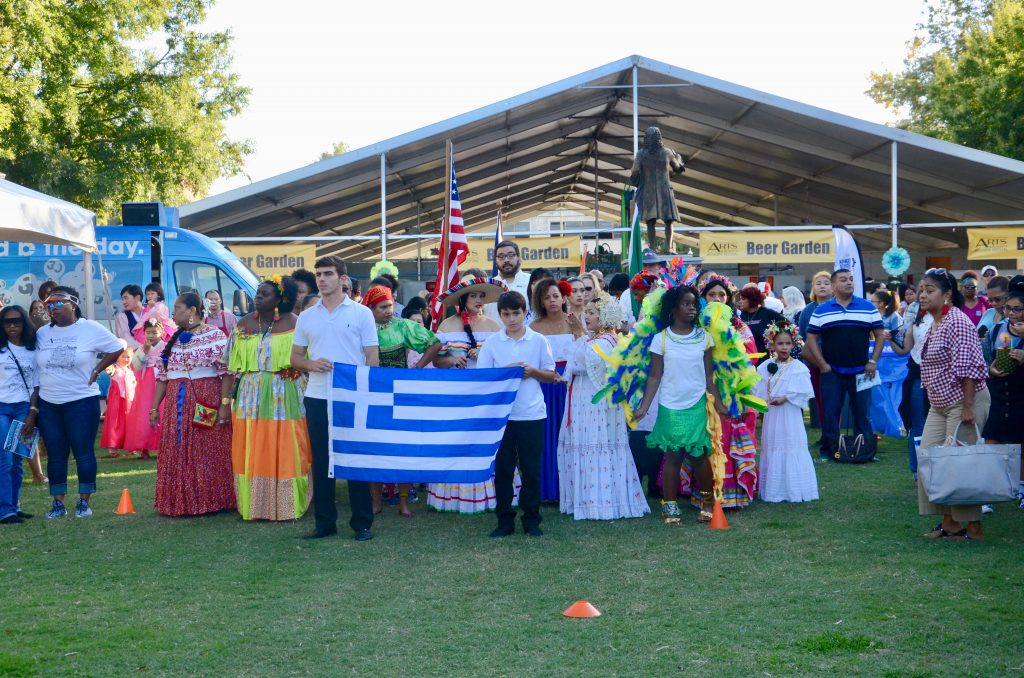 A collection of people ranging in age from small children to older adults, in ethnic dress from Greece, Jamaica, Latin America, and other parts of the world. The Greek flag is prominent in the foreground.