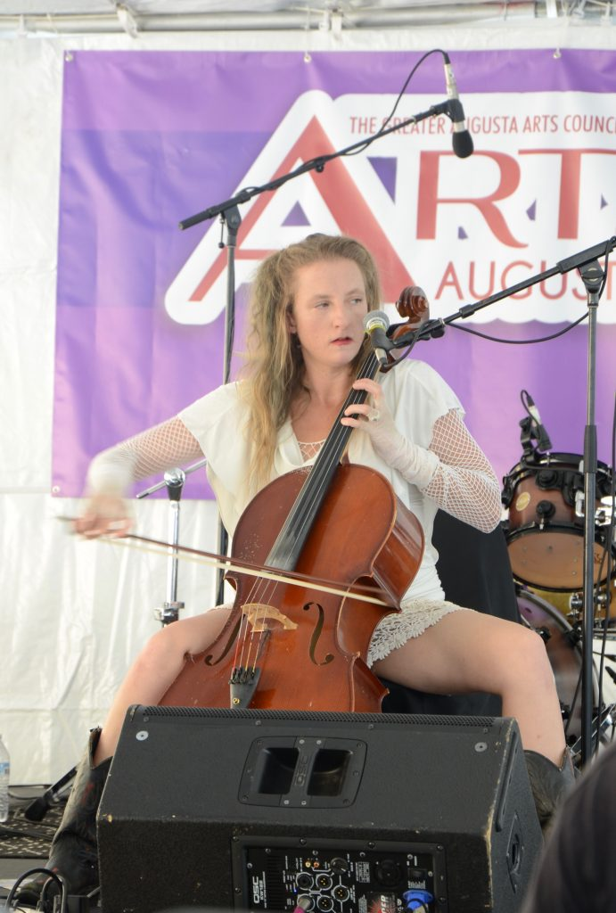 A woman of European decent, wearing an off-white dress and shorts, and playing a chello and singing. Her legs are wide to accommodate the instrument and her hands are blurred as she plays hard and fast.