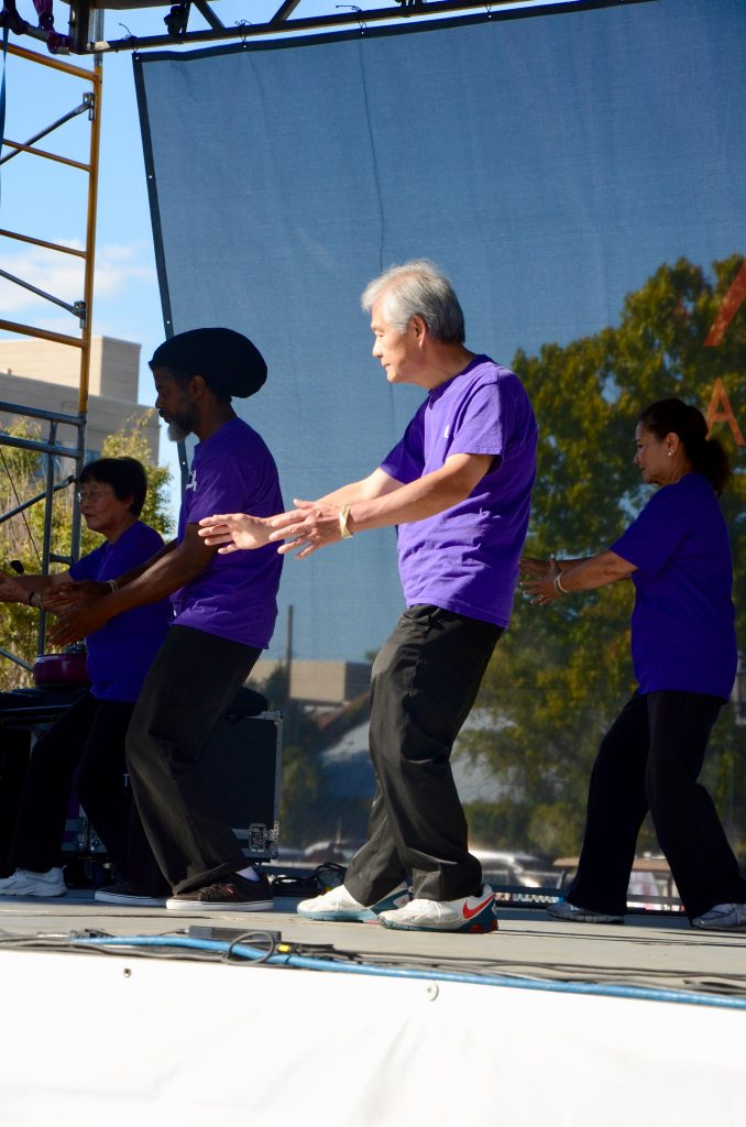 An older main from China doing a Tai Chi demonstration with a group. Each wearing matching purple shirts and black pants.