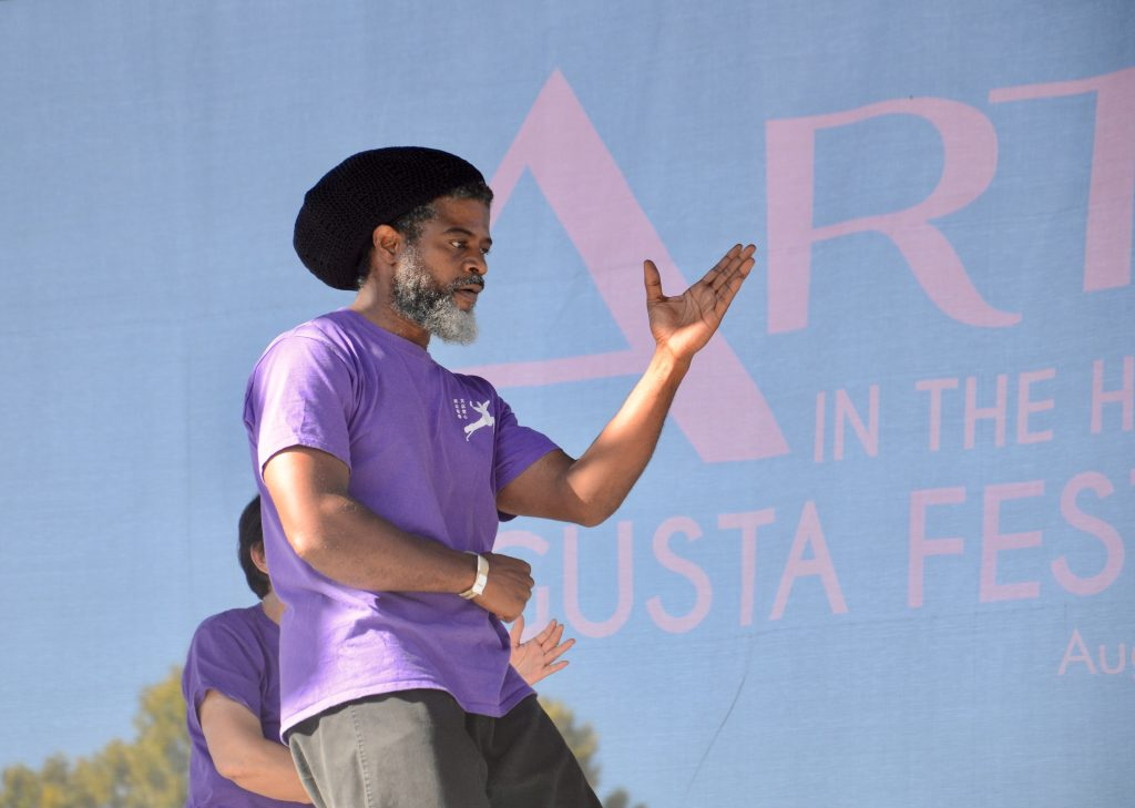 An African American man performing with the group from the Chinese community wearing the purple shirt from the Tai Chi demonstration.