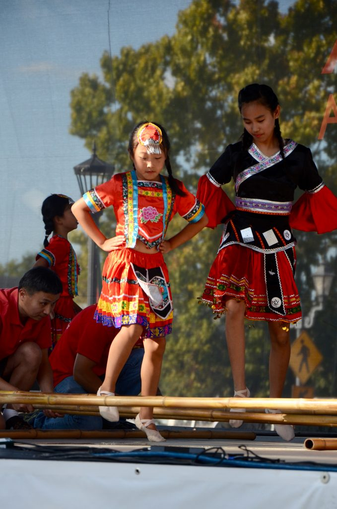 Young girls of Chinese decent, dressed in bright red and block costumes dance over a series of bamboo bars.