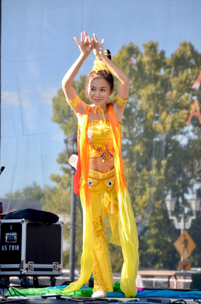The Chinese woman in yellow is facing the camera as she dances with her hands raised above her head.