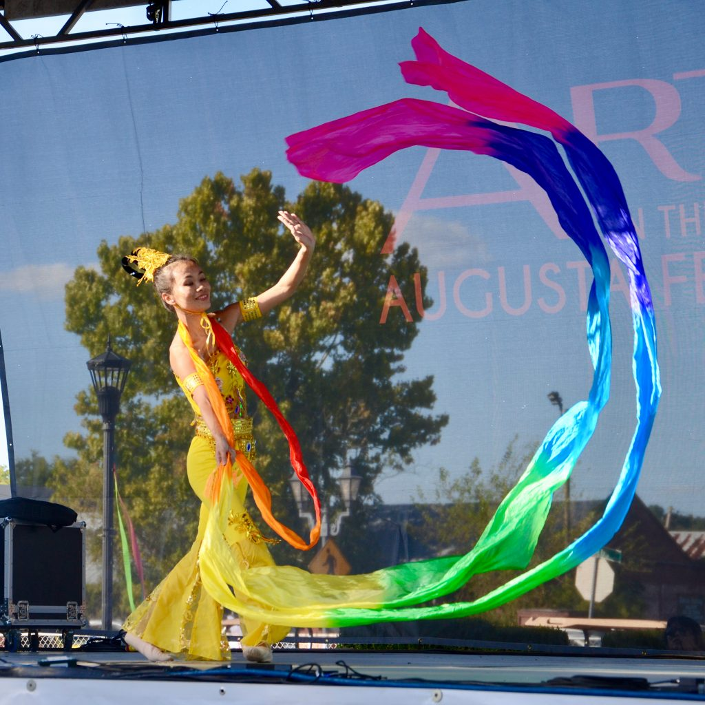 A woman from China, in a bright yellow dress, dances with long rainbow streamers flying in an arch in front of her.