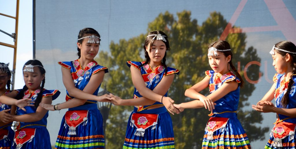 A group of girls of Chinese decent in matching blue costumes hold hands as they perform a dance on the main stage.