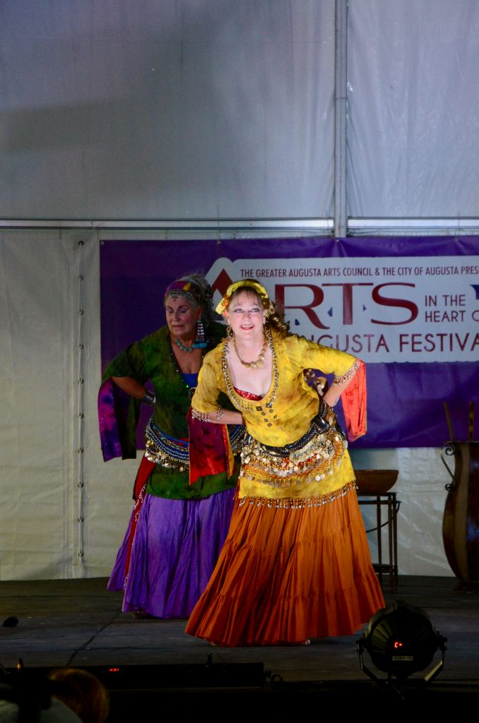 A belly dancer in a yellow costume dominates the stage as she leans forward in her dance.