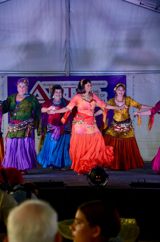 A belly dance troop dancing on a side stage. Women of various backgrounds are shown dancing in a generally middle eastern style of dress and movement.