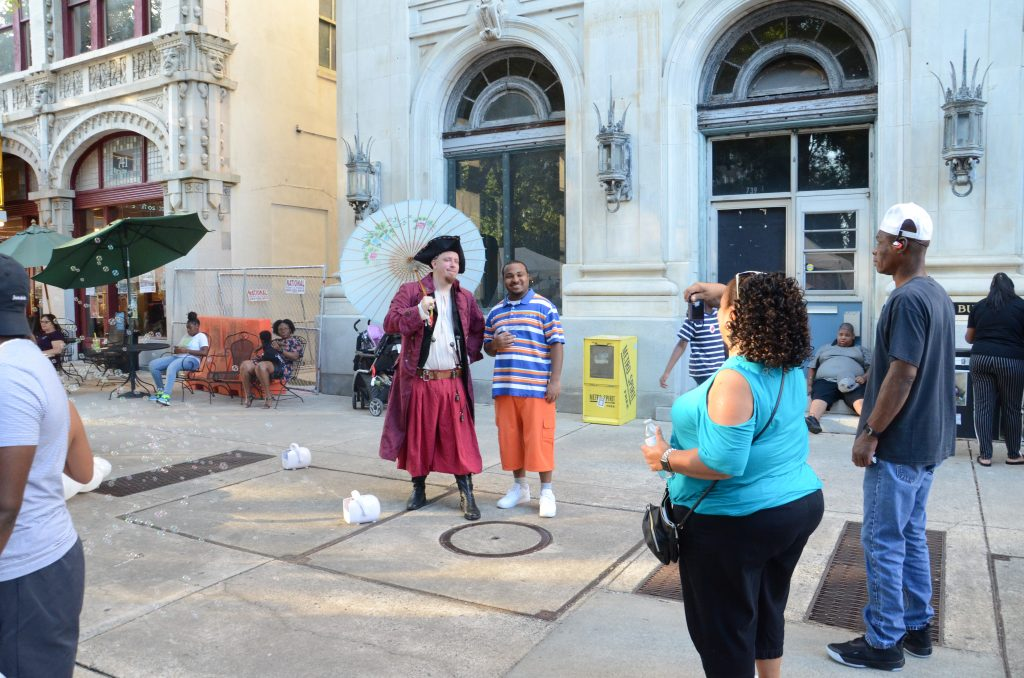 The man dressed as a pirate, holding a white parasole, is having his picture taken with an African American festival goer.