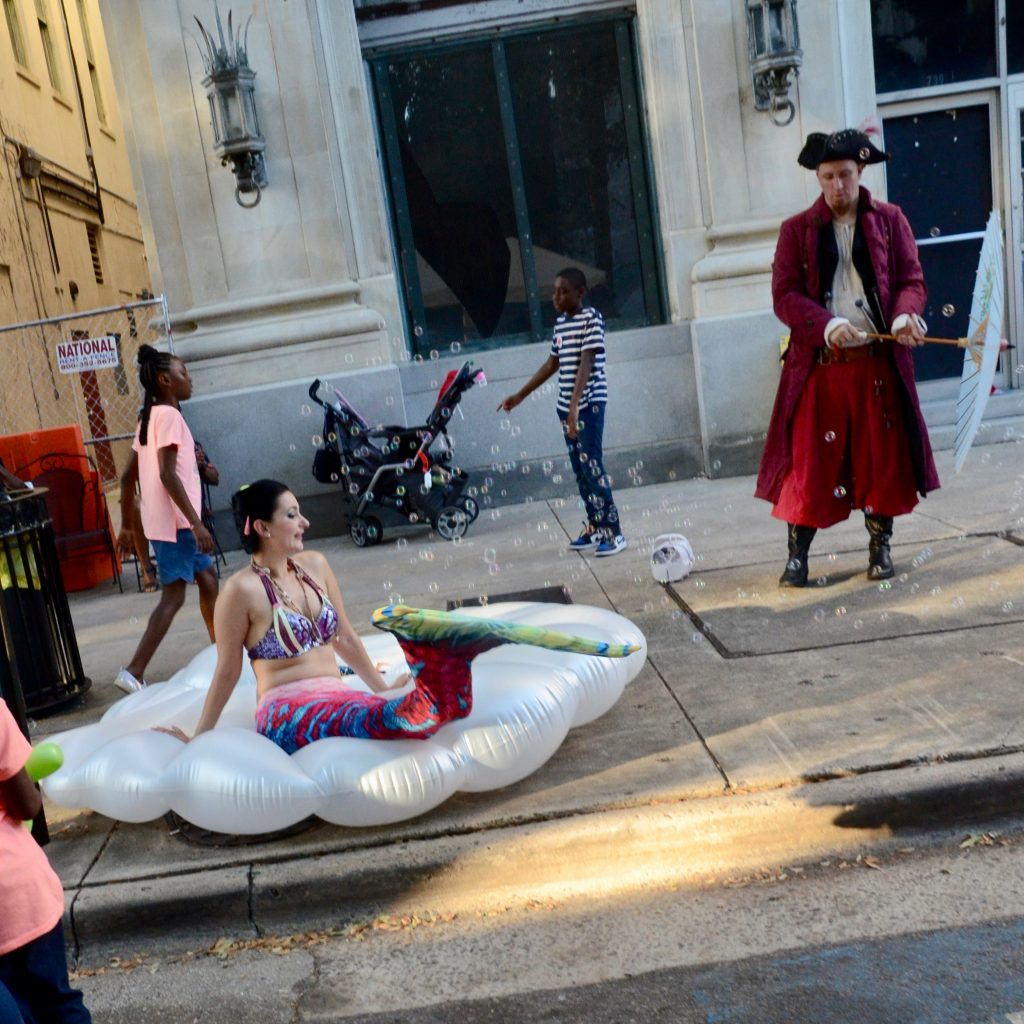 A woman of European decent is dressed as a mermaid is sitting on a large inflatable clamshell while two machines blow bubbles over her and a man, also of European decent, dress as a pirate looks on while holding parasole.