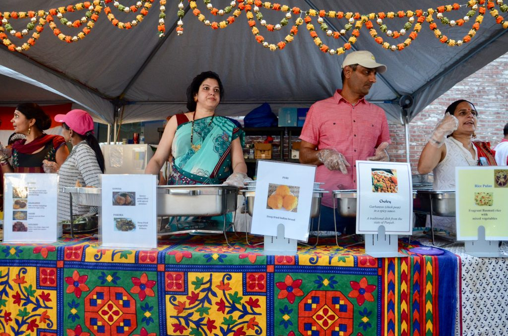 Several Indian immigrants standing at their food table selling vegetarian dishes that are always highly popular. Descriptions of their dishes are shown in front of each chaffing dish.