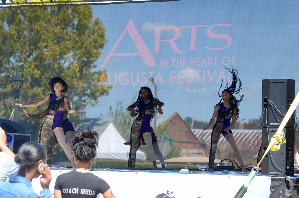 A troop of African American girls dancing on the main stage, their hair is flying as they move with energy.