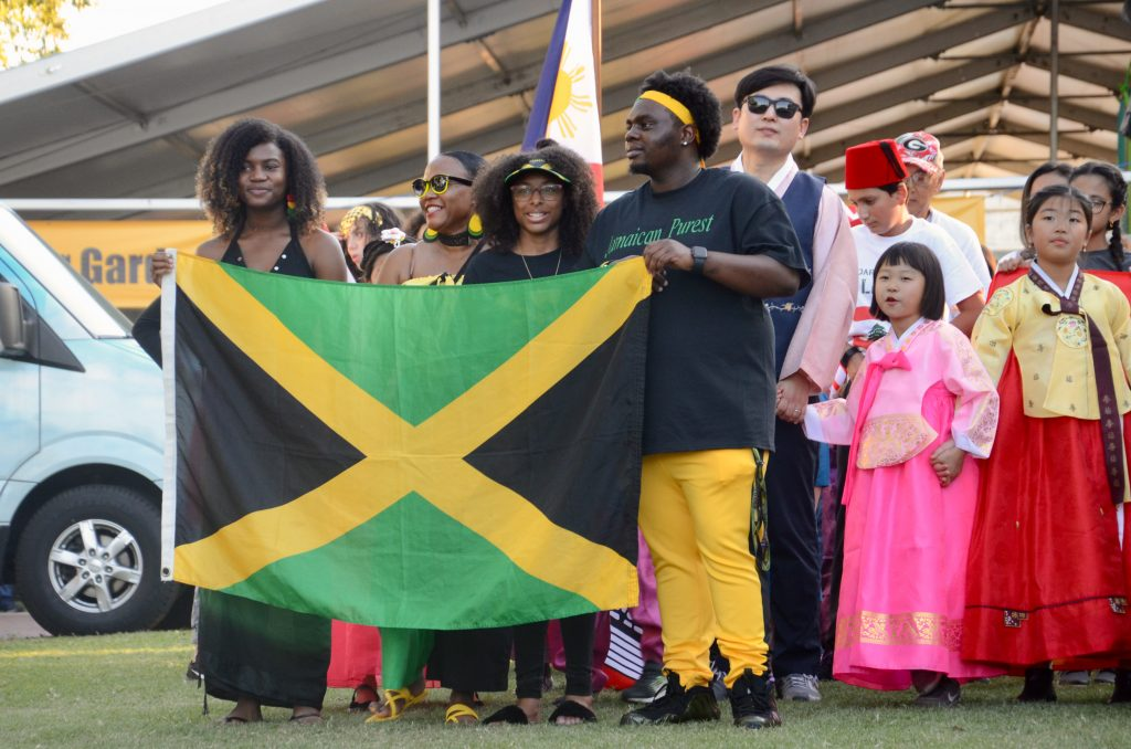A group of people of Jamaican decent hold a large Jamaican flag.