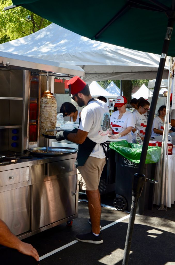 A man wearing a tarboush (Lebanese hat) cutting chicken from a shawarma for sale at the Lebanon food tent.