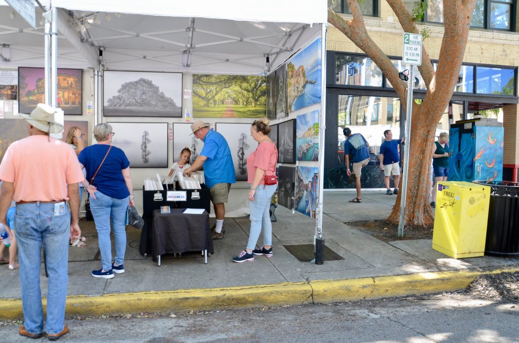Festival goers reviewing paintings for sale at a booth. A young girl and older gentleman (maybe her grandfather) are looking together as some images in a collection not mounted on the booth wall.