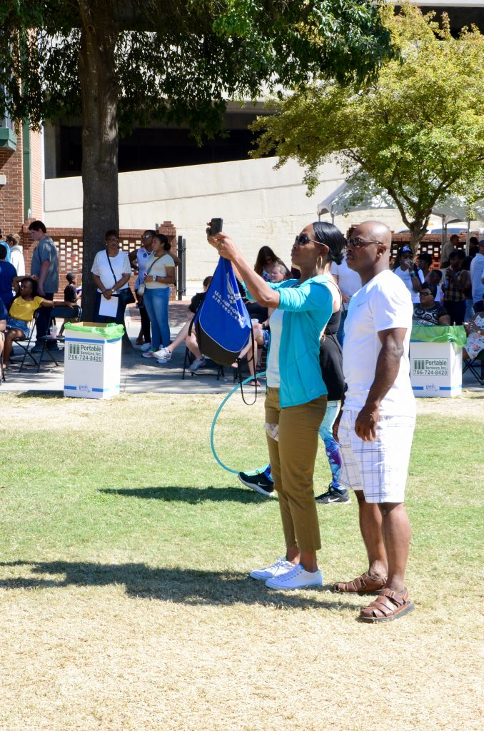 An African American couple stands on the green watching a performance. She is holding a phone to record the moment, he is simply watching and smiling.