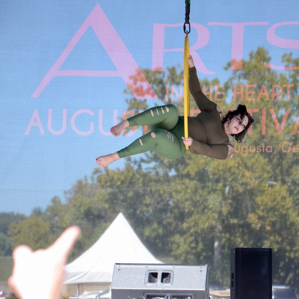 A woman in green and brown performs in the suspended ring, a finger in the foreground is pointing at the performer.
