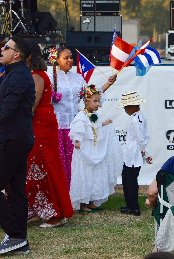 Two small children in traditional Cuban clothes, dance with a large group of adults. The adults are waving flags from several countries.