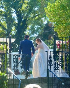 Newly married couple walking away from the camera have walked passed a metal fence.