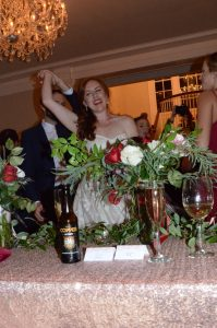 A couple dancing at their wedding, the bride is smiling as they do a spin. In the foreground is their table with their place cards, drinks, and flowers showing.