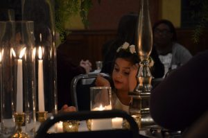 A flower girl seated at dinner, the picture is taken carefully around the table decorations.